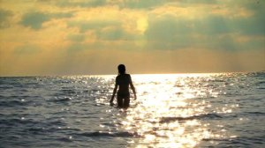 stock-footage-woman-walking-into-the-sea-at-sunset